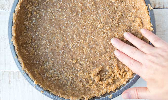unbaked crust for sugar free pumpkin pie with hand
