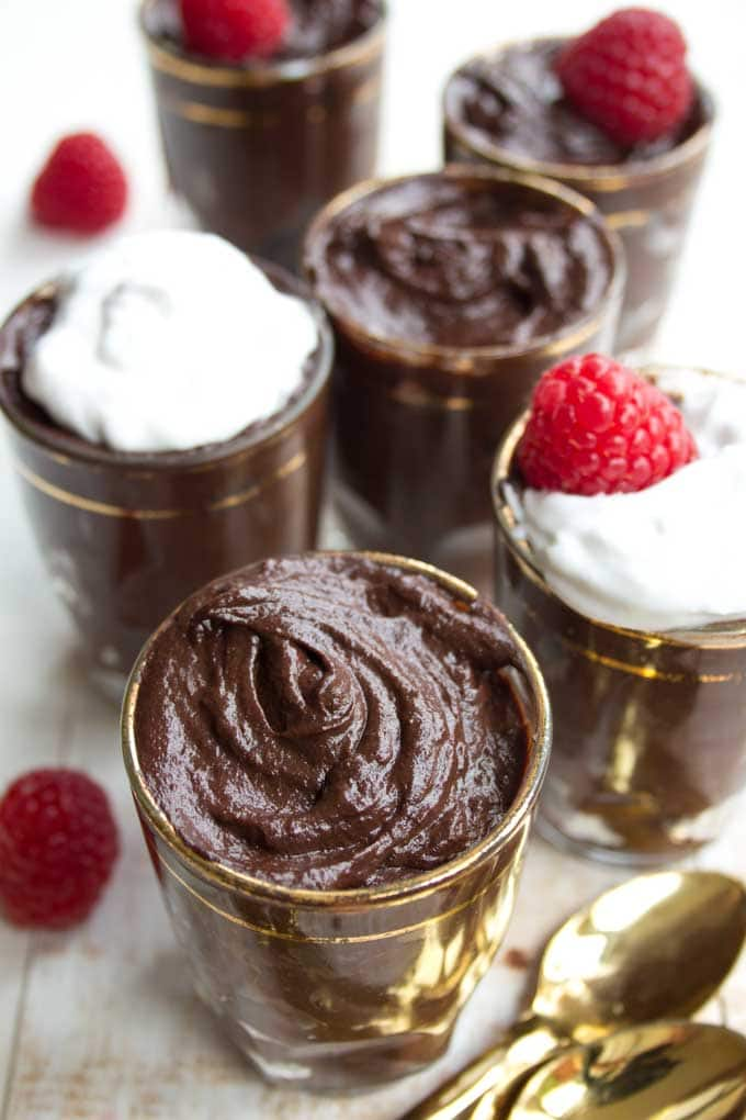 glasses with chocolate avocado mousse decorated with raspberries and spoons on the side
