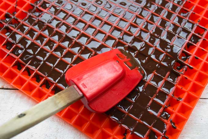 Spreading sugar free chocolate into the silicone mat with a spatula