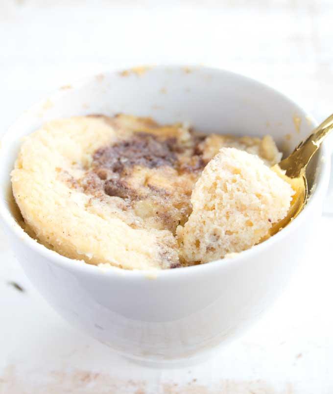 cinnamon swirl coconut flour mug cake with a spoon