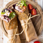 Flaxseed keto wraps filled with ham and cheese on a wooden board