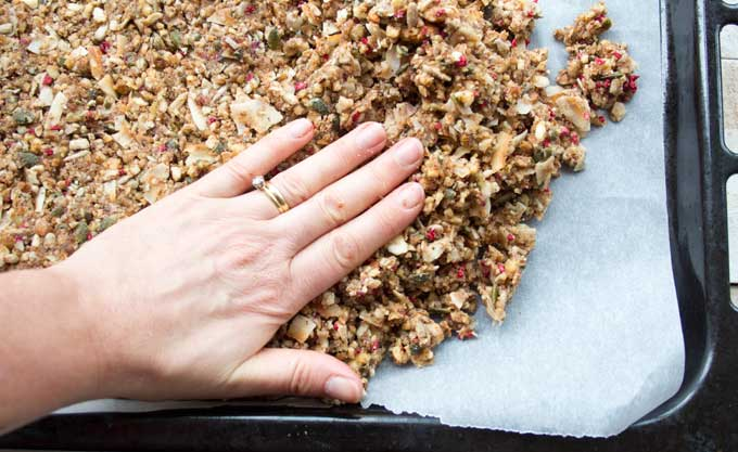 pressing the low carb granola mix onto a baking sheet