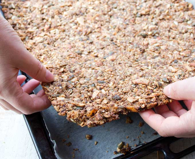 lifting baked low carb granola off the baking tray
