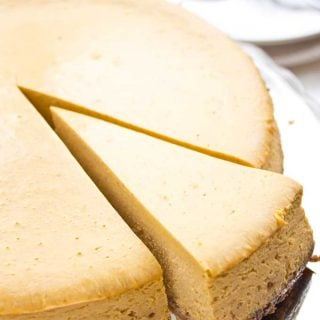 taking a slice from a keto pumpkin cheesecake