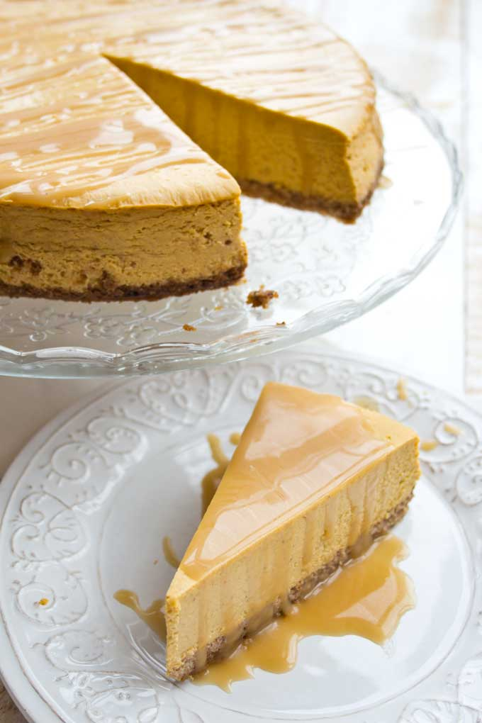 a low carb pumpkin cheesecake on a cake stand and a slice of pumpkin cheesecake