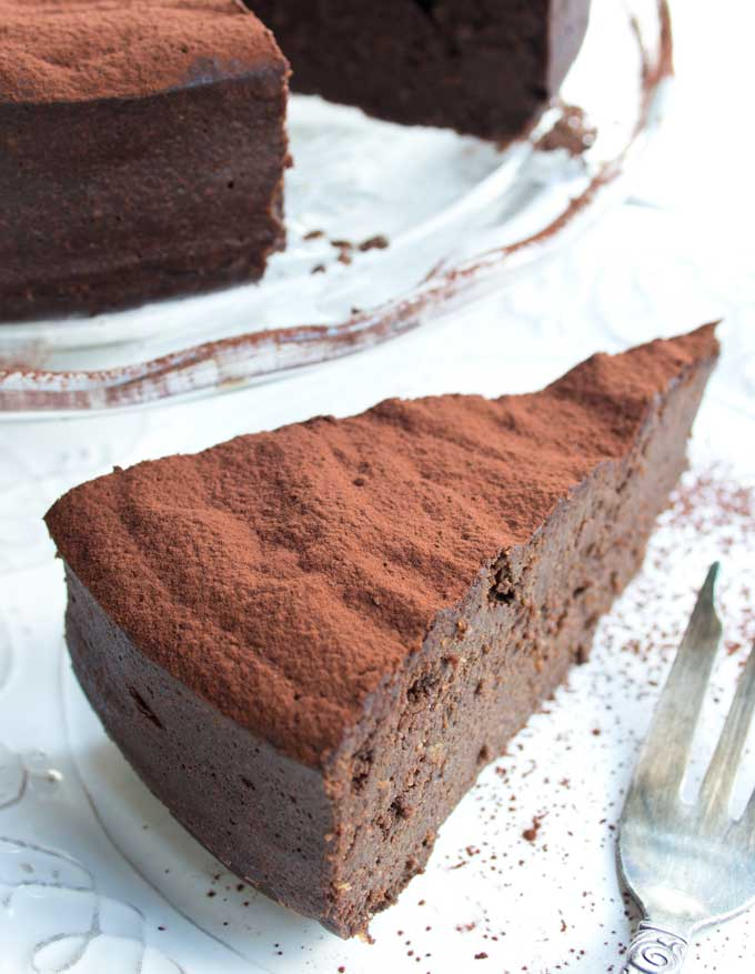 a slice of cake dusted with cocoa powder on a plate and a fork