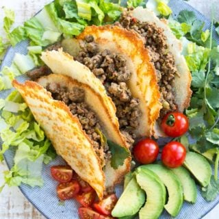 Three Keto taco shells on a plate filled with Taco ground beef and surrounded by salad on a plate