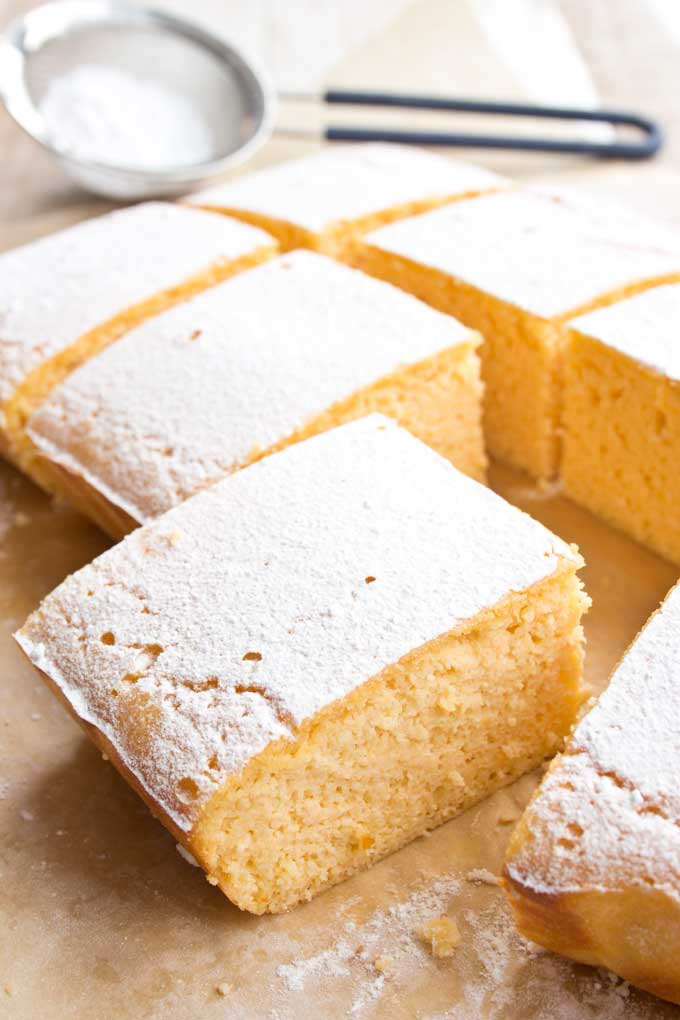 a rectangular Keto lemon cake cut into slices and topped with powdered sweetener