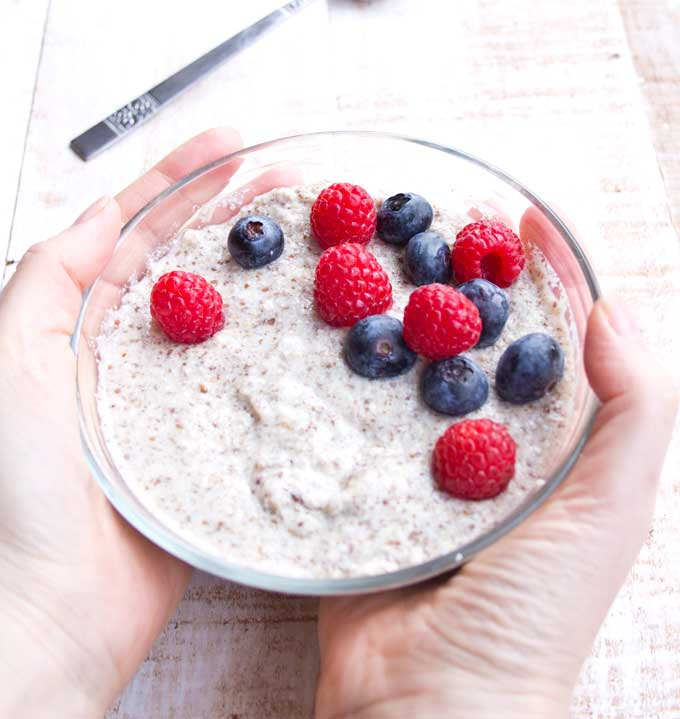 two hands holding a bowl of keto low carb porridge decorated with blueberries and raspberries