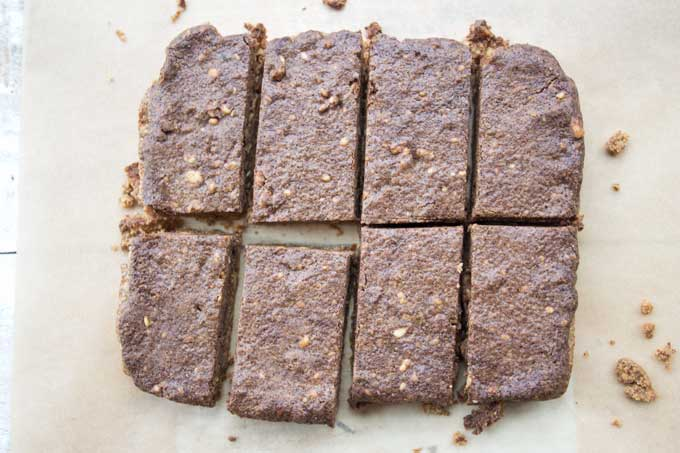 peanut butter protein bars cut into 8 slices on parchment paper