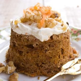 a keto carrot cake turned out onto a plate decorated with cream cheese frosting, carrot shavings and crushed walnuts and a spoon