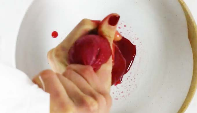 hands squeezing berry juice with a muslin into a bowl