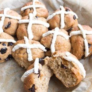 Keto hot cross buns in a baking tray with one bun broken in half
