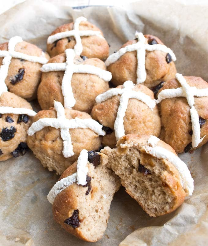 Keto hot cross buns in a baking tray with one bun broken in half