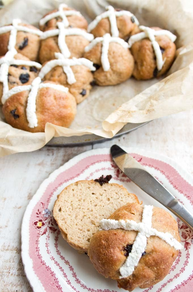 a plate with a hot cross bun cut in half with more hot cross buns in the background
