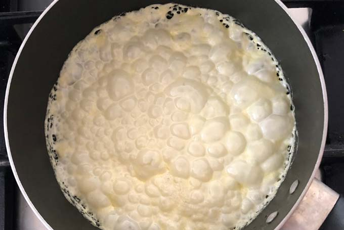 bubbling cream being reduced in a frying pan