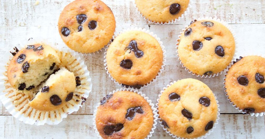 a bunch of chocolate chip muffins with one broken in half inside its open white paper case on a wooden table