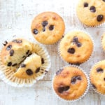 almond flour muffins with chocolate chips on a white wooden surface
