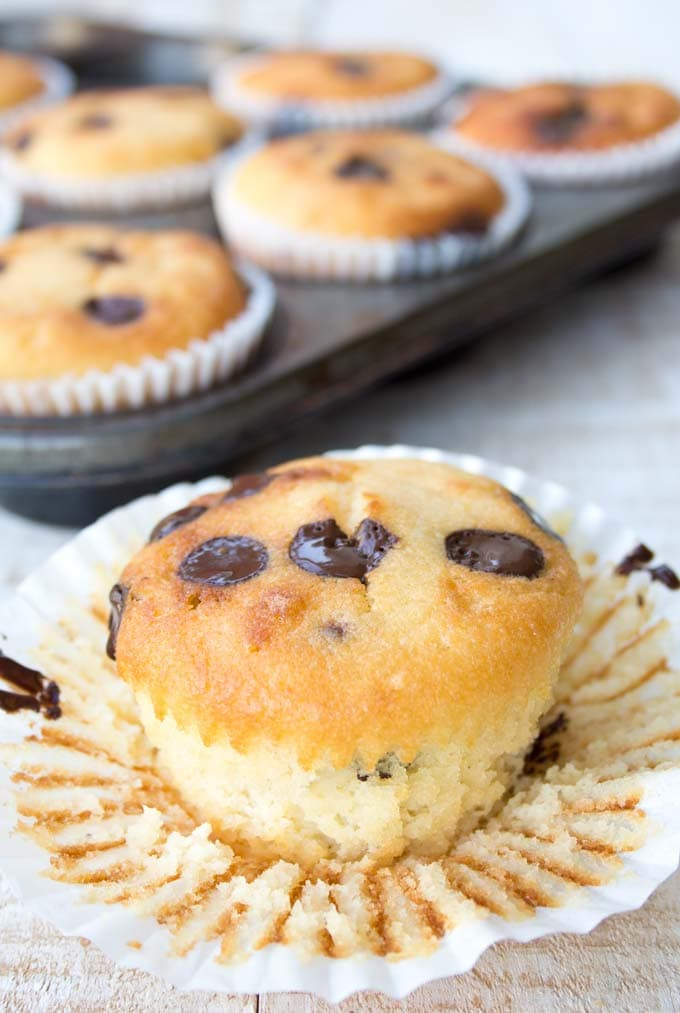 closeup of a chocolate chip muffin with the white paper case opened and more muffins in the background