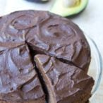 a cake server taking a slice of chocolate avocado cake with chocolate frosting from a cake on a glass tray with avocado halves in the background