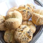 A silver tray with baked rolls topped with a mix of poppy seeds and sesame seeds