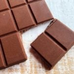 closeup of two pieces of keto milk chocolate tha have been broken off from a bar of homemade sugar free chocolate