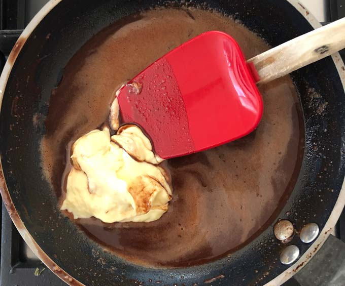 a red silicone spatula stirring double cream into liquid cocoa mass in a black pan