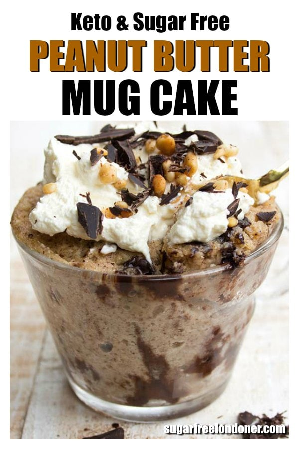 a peanut butter mug cake in a glass mug decorated with whipped cream and a golden spoon