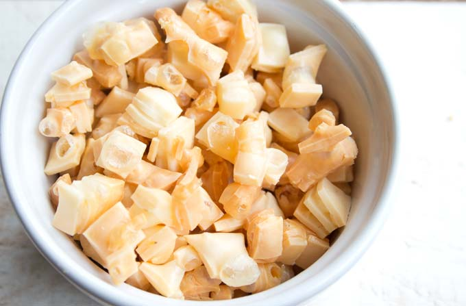 Sliced cheddar cut into squares and puffed in the oven in a white bowl