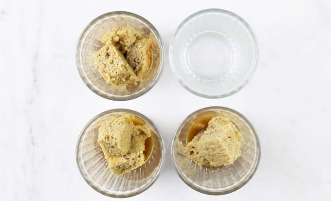 three of four glasses on a table are filled with coffee-soaked sponge cake squares