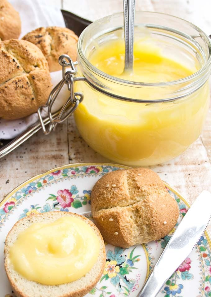 a roll spread with lemon curd on a plate with a knife and a mason jar filled with lemon curd and a silver tray with more rolls in the background