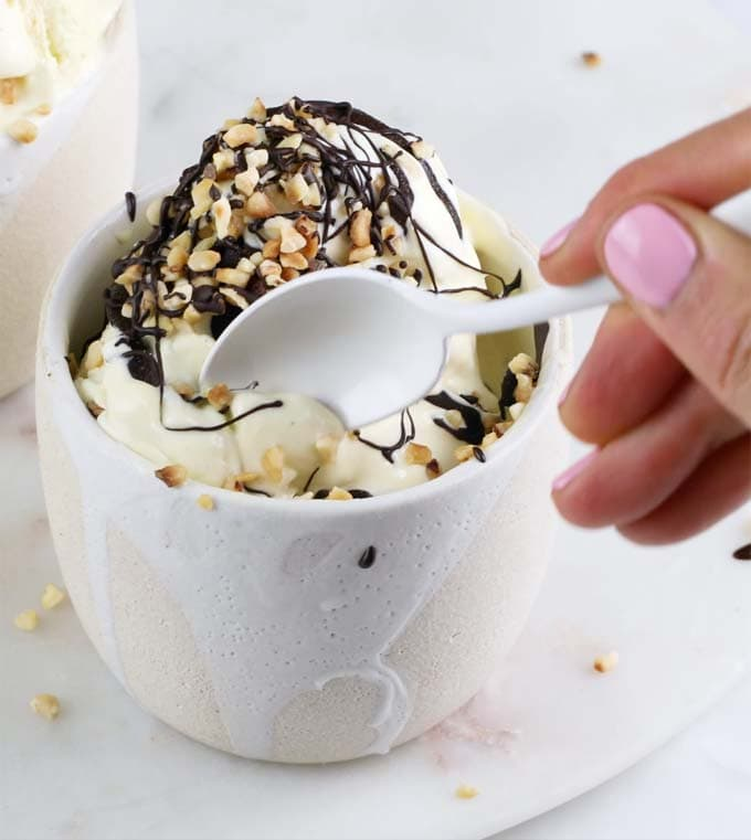 A hand taking a spoonful of vanilla ice cream decorated with chocolate and nuts