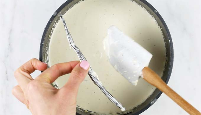 removing the vanilla bean from the cream mix after infusing in a pot by hand with a spatula
