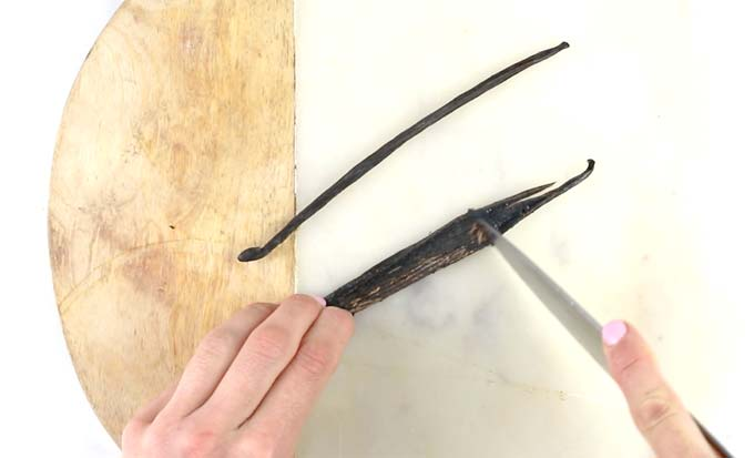 Two hands cutting a vanilla bean with a knife on a cutting board, scooping out the seeds