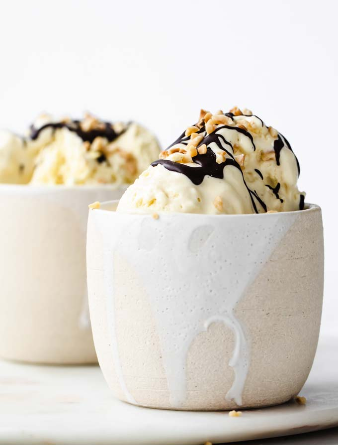 Two white ceramic dessert bowl with homemade low carb vanilla ice cream, decorated with a chocolate drizzle and chopped nuts