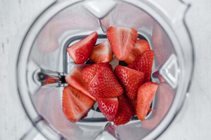 strawberry halves in a food processor bowl