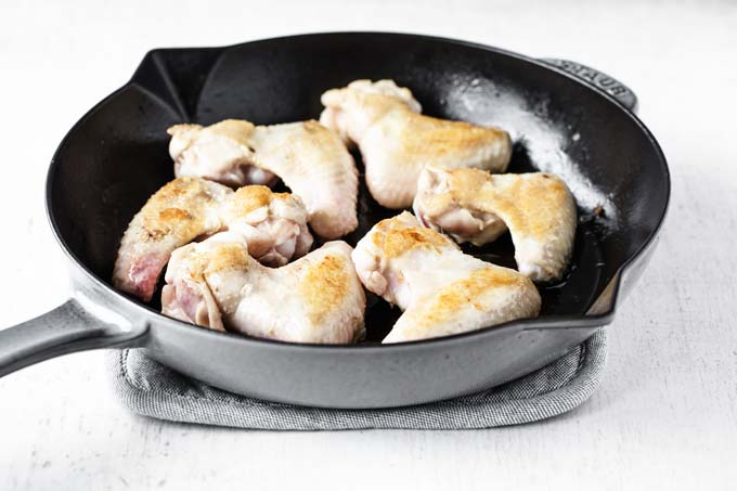 browning chicken pieces in a frying pan