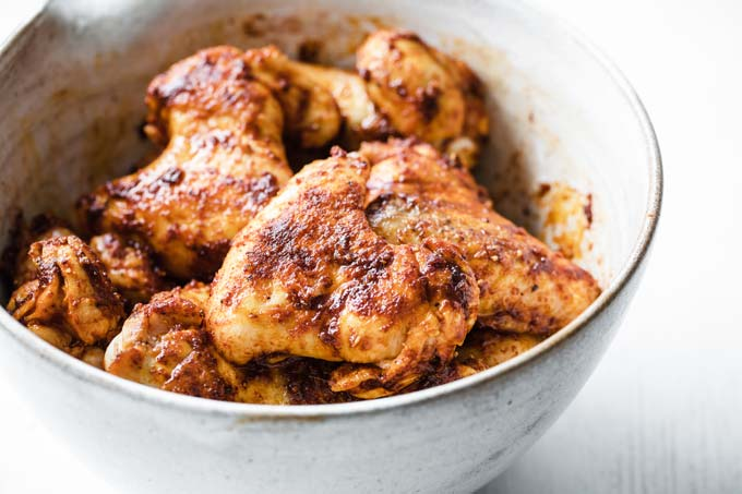a bowl with browned chicken wings covered in bbq spice wrap before baking