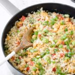 Closeup of cauliflower fried rice with spring onions and pepper in a cast iron pan