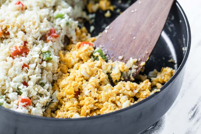 a pan with riced cauliflower one side and scrambled eggs with a spatula on the other side