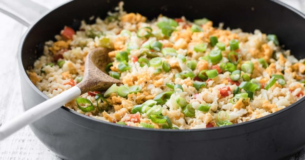 a pan with cauliflower egg fried rice and a wooden spoon