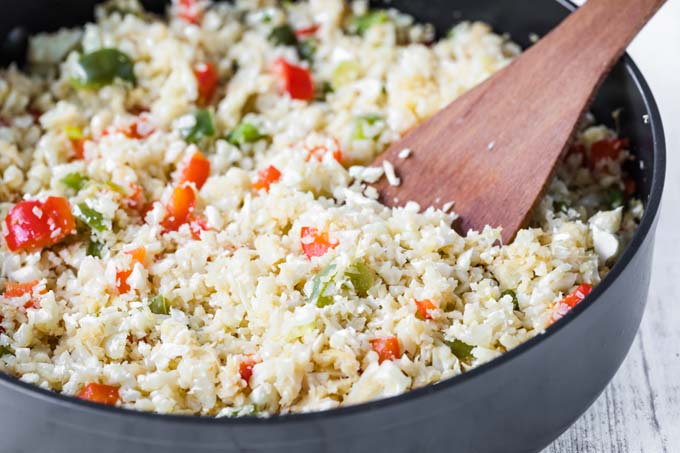 cauliflower rice and vegetables in a pan and a spatula