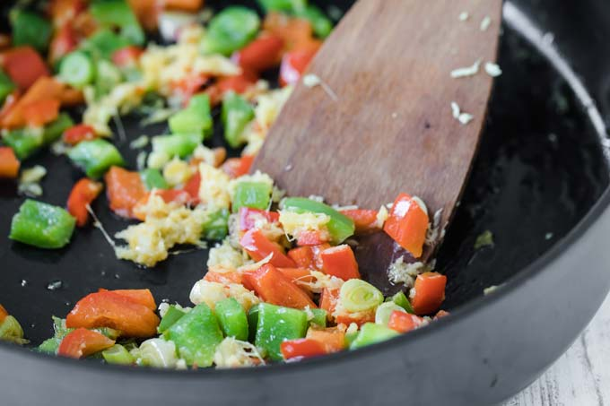 chopped vegetables in a frying pan with a spatula