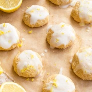 Keto lemon cookies with a lemon glaze and sprinkled with zest on a sheet of baking paper and lemon halves