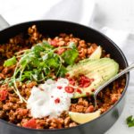 low carb chili with turkey mince in a pan topped with coriander, avocado and sour cream and a spatula