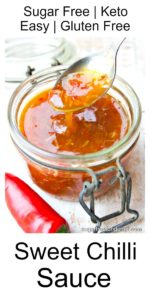a glass jar with sugar free sweet chilli sauce and a spoon dripping with sauce with a red chilli on the side