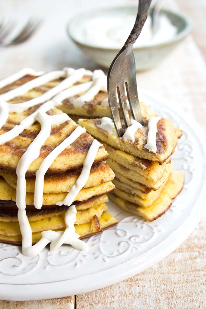 a fork taking a slice of a stack of low carb pancakes with a cinnamon swirl and cream cheese frosting