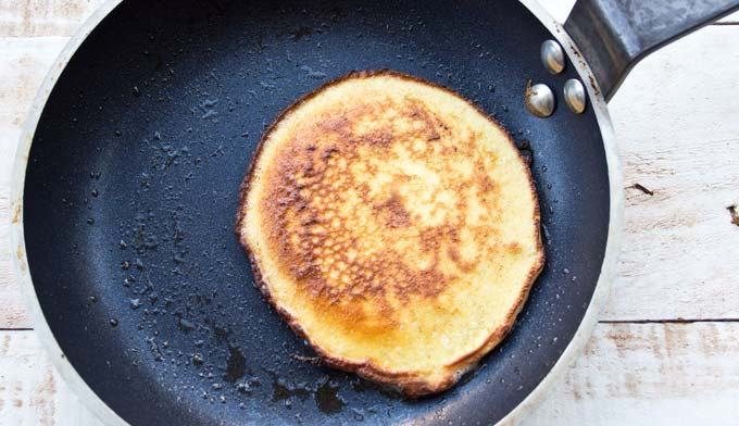 a browned almond flour cream cheese pancake in a frying pan