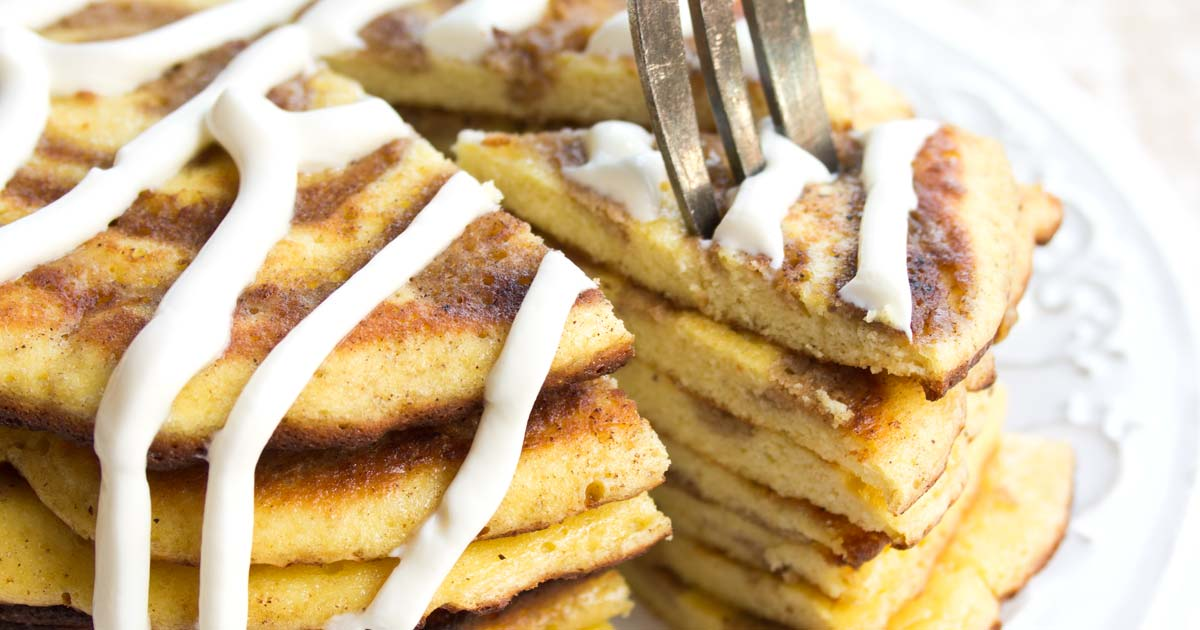 closeup of a a fork taking a slice of a stack of low carb pancakes with a cinnamon swirl and covered in cream cheese frosting