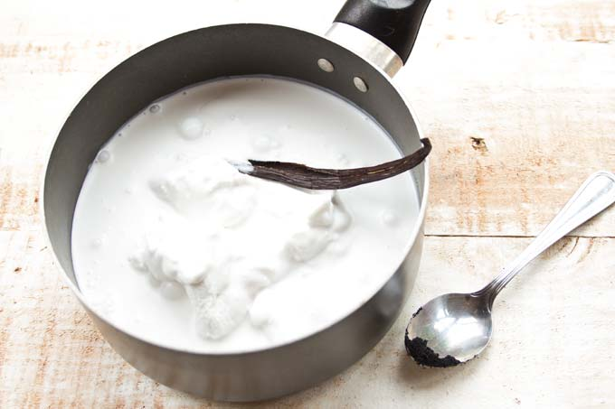 coconut cream and a vanilla pod in a saucepan